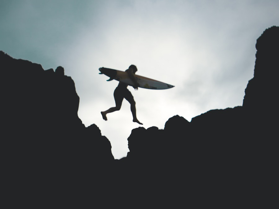 Black and white image of The Surfing Copywriter jumping between two rocks