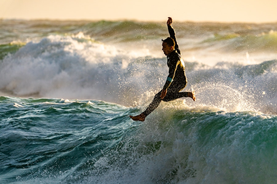 Surf camp blog writer jumping from the top of a wave.