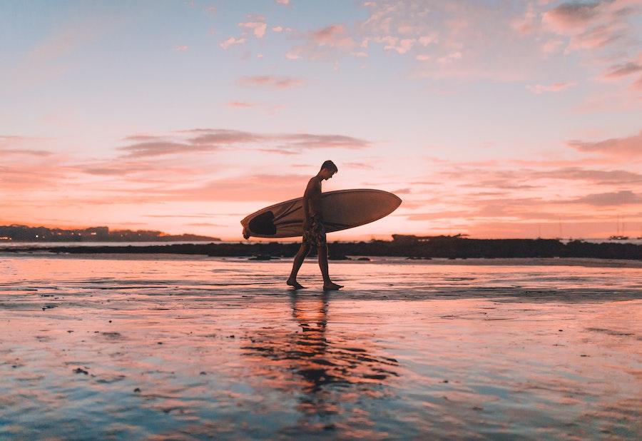 Man with surfboard walking along beach at sunset